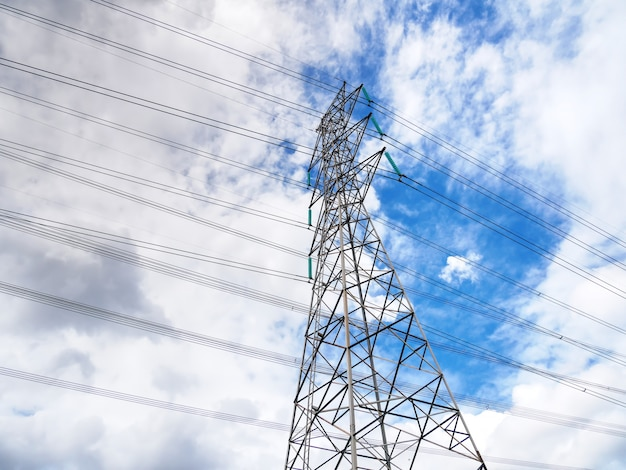 Lage hoekmening van hoogspanningsmasterstructuur en machtslijnen tegen blauwe bewolkte hemel Premium Foto