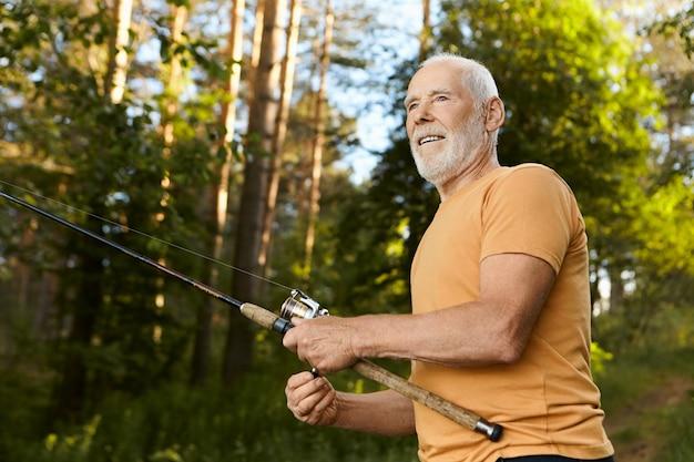 Lage hoekmening van knappe bejaarde 60-jarige man met dikke grijze baard met vrolijke gelaatsuitdrukking, vis uit het water trekken tijdens het vissen op het meer, zomerochtend buitenshuis doorbrengen Gratis Foto