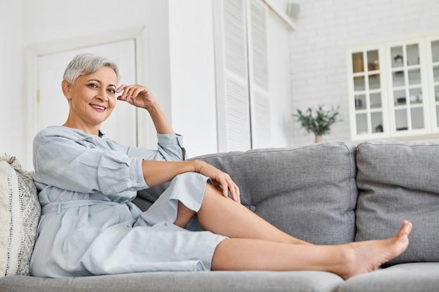 Lage hoekmening van modieuze elegante volwassen zestig jaar oude blanke vrouw met korte pixie kapsel ontspannen thuis zittend op de grijze bank in haar ruime gezellige schone woonkamer, glimlachend Gratis Foto