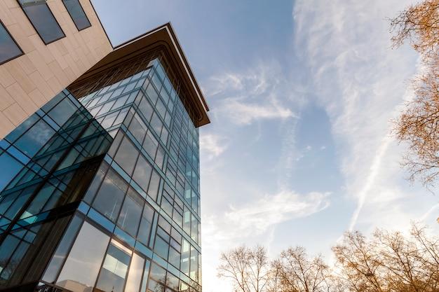 Lage hoekmening van weerspiegeling van blauwe hemel in glasmuur van moderne de bureaubouw wolkenkrabber in bedrijfsdistrict Premium Foto