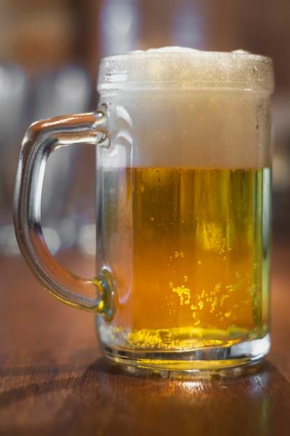 Lage hoekpint met bier op lijst Gratis Foto