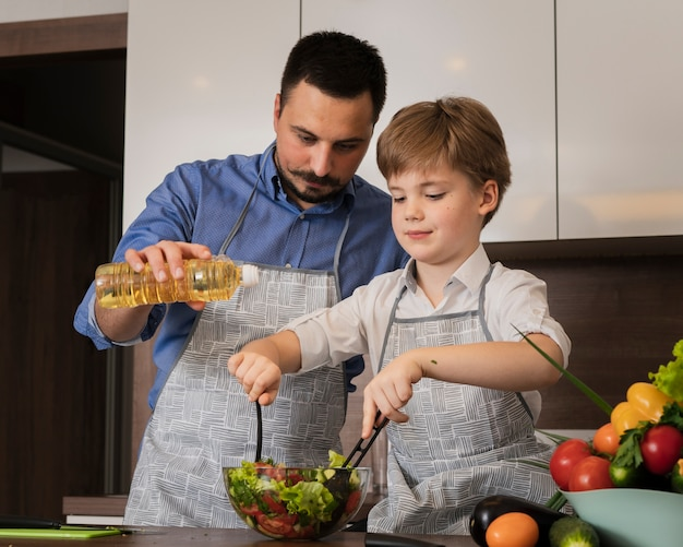 Lage hoekvader en zoon die salade maken Gratis Foto