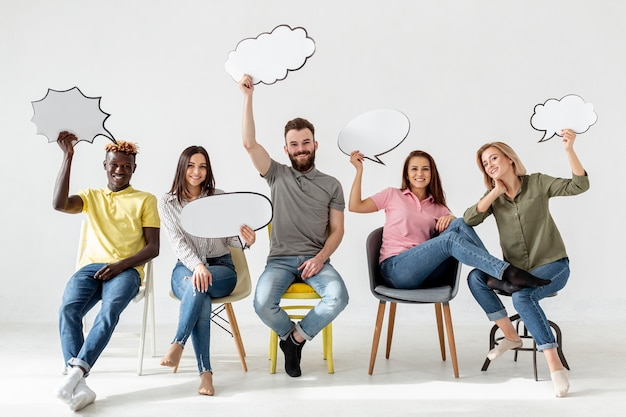 Lage hoekvrienden op stoelen met praatjebellen Gratis Foto