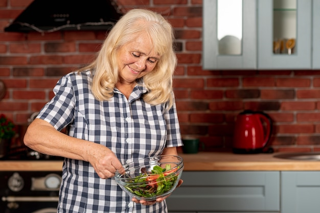 Lage hoekvrouw die salade mengt Gratis Foto