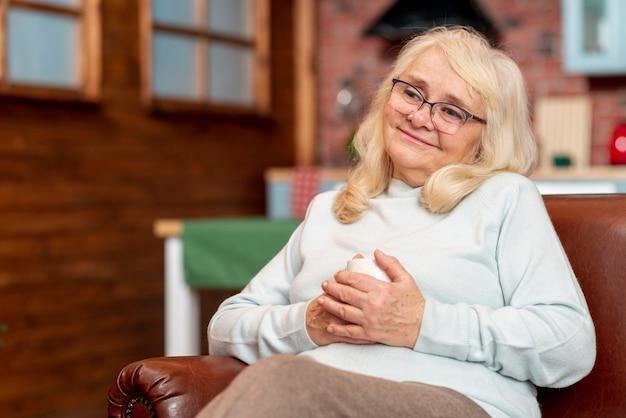 Lage hoekvrouw die thuis thee drinkt Gratis Foto