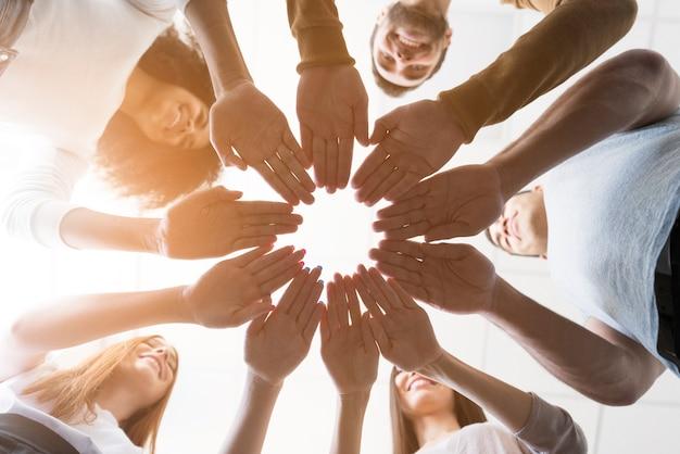 Lage kijkgemeenschap van mensen die handen aanraken Gratis Foto