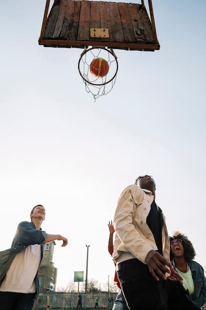 Lage meningsgroep vrienden die basketbal in openlucht spelen Gratis Foto
