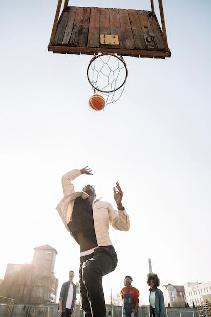Lage meningsvrienden die basketbal in openlucht spelen Gratis Foto