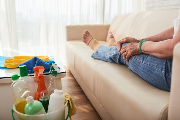 Lage sectie die van bebouwde onherkenbare vrouw op bank na huis het schoonmaken rust Gratis Foto