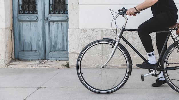 Lage sectie van een man die de fiets op straat berijdt Gratis Foto