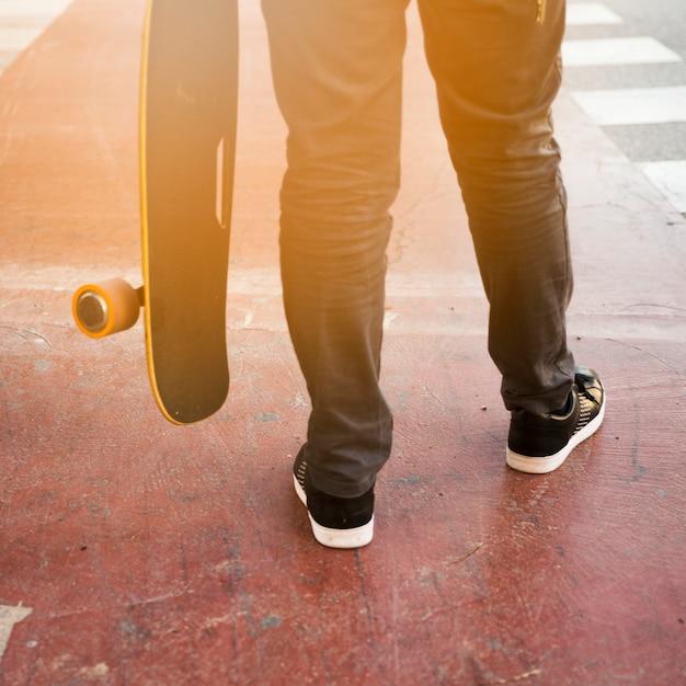 Lage sectie van een skateboard van de persoonsholding Gratis Foto