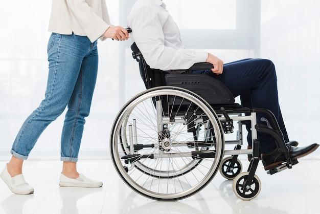 Lage sectie van een vrouw die de man zittend op rolstoel duwen Gratis Foto