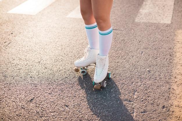 Lage sectie van een vrouw die rolschaats draagt die zich op asfalt bevindt Gratis Foto