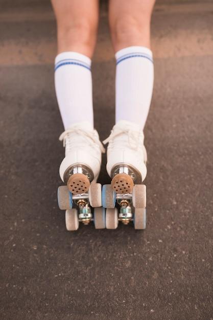 Lage sectie van het been van de vrouw die rolschaats op asfalt draagt Gratis Foto