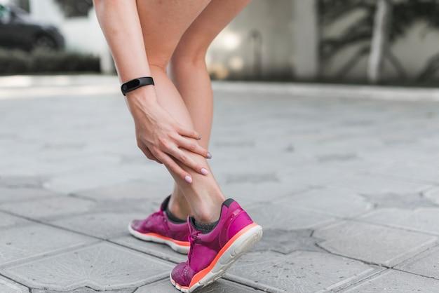 Lage sectie van vrouwelijke atleet die zich op straat bevindt die pijn in enkel heeft Gratis Foto