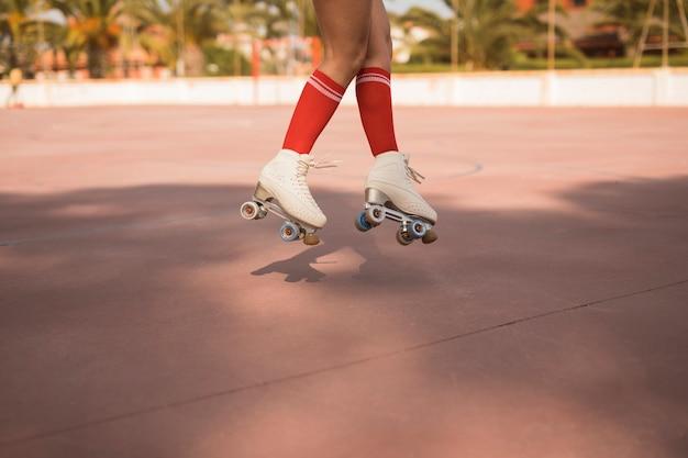 Lage sectie van vrouwelijke dragende witte rolschaats die in lucht springt Gratis Foto