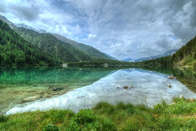 Lake in de buurt van berg bedekt met bomen Gratis Foto
