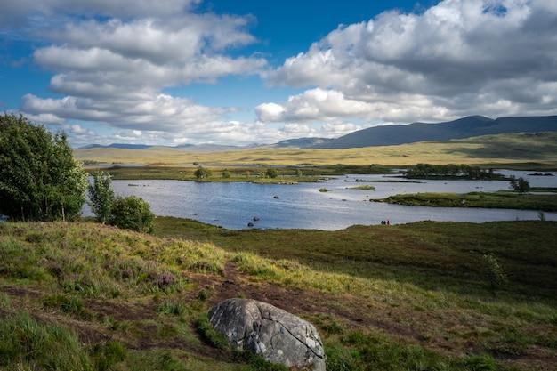 Lake loch tulla omgeven door bergen en weilanden in het vk Gratis Foto