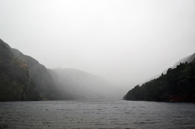 Lake omgeven door heuvels onder de mistige grijze lucht Gratis Foto