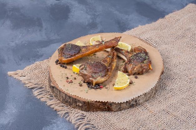 Lamchomps op een houten bord met plakjes citroen en bestek op tafellaken. Gratis Foto
