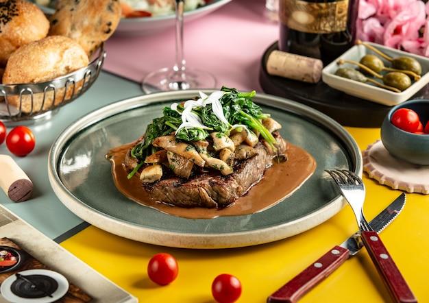 Lamsbiefstuk gegarneerd met gebakken champignons en spinazie Gratis Foto