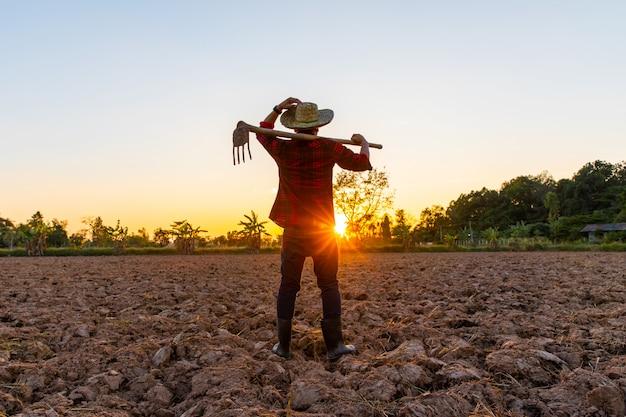 Landbouwer die aan gebied bij zonsondergang werkt openlucht Premium Foto