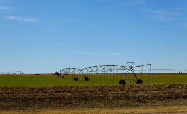 Landbouwirrigatiesysteem het water geven gebied op zonnige dag. Premium Foto