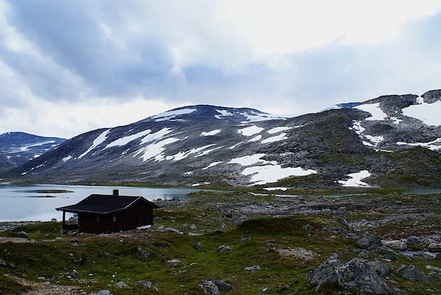 Landelijk noors huisje in de buurt van een meer, omringd door hoge rotsachtige bergen aan de atlantic ocean road, noorwegen Gratis Foto