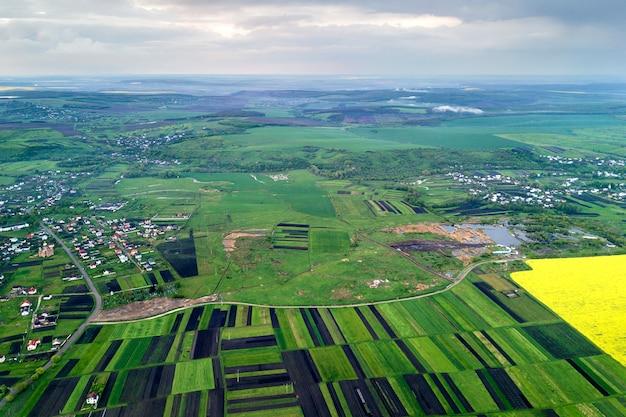 Landelijke omgeving op lente of zomerdag. luchtfoto van groene, geploegde en bloeiende velden, huis daken op zonnige dageraad. drone fotografie. Premium Foto