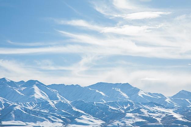 Landschap besneeuwde bergen met blauwe lucht en wolken Premium Foto
