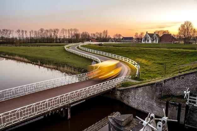 Landschap dat van een brug over een kanaal in een groene buurt is ontsproten Gratis Foto