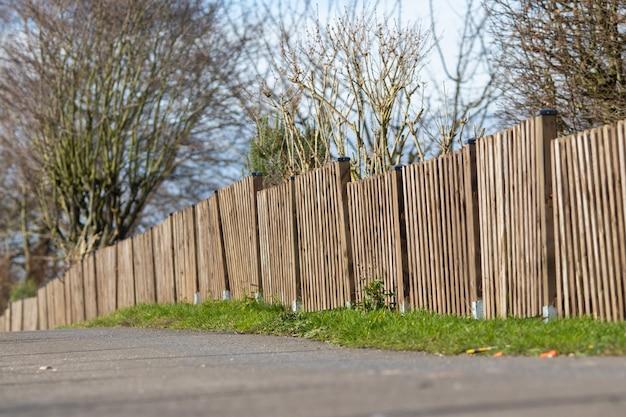 Landschap dat van een bruine houten omheining van een minibos is ontsproten met een duidelijke blauwe hemel Gratis Foto