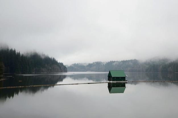 Landschap dat van een meer is ontsproten met een klein groen drijvend huis in het midden tijdens mistig weer Gratis Foto