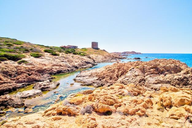 Landschap dat van rotsachtige heuvels met kasteelgebouw is ontsproten dichtbij de open zee met een duidelijke zonnige blauwe hemel Gratis Foto