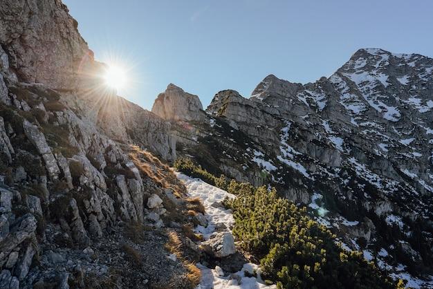 Landschap dat van sneeuwbergen is ontsproten met de zon die glanst Gratis Foto