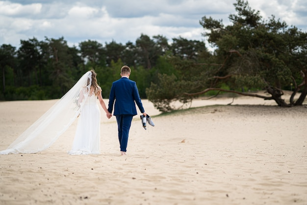 Landschap shot van een paar wandelen op zand op hun trouwdag Gratis Foto