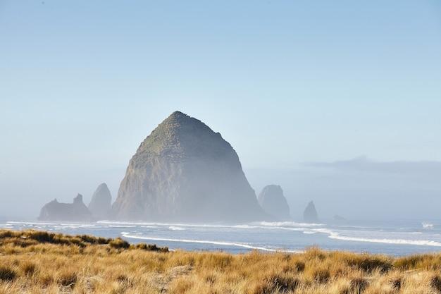 Landschap van de hooibergrots in de ochtendmist bij cannon beach, oregon Gratis Foto