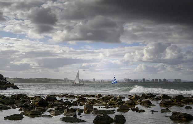 Landschap van de kust omgeven door de zee met schepen en surfers erop onder een bewolkte hemel Gratis Foto