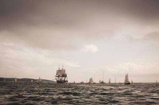 Landschap van de zee met zeilschepen erop onder een bewolkte hemel in de avond Gratis Foto