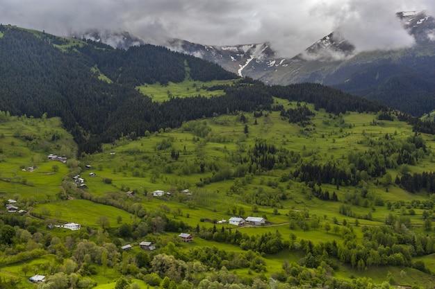 Landschap van heuvels bedekt met bossen en mist onder de bewolkte hemel Gratis Foto