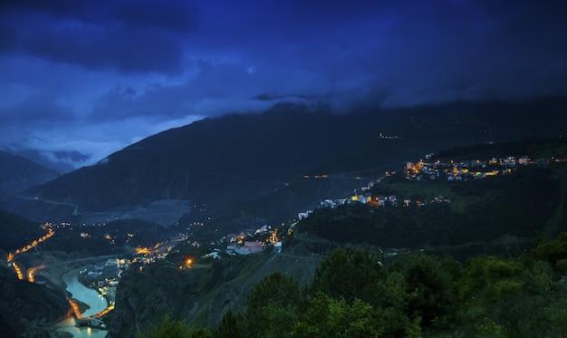 Landschap van heuvels bedekt met gebouwen en bossen onder een bewolkte hemel tijdens de nacht Gratis Foto