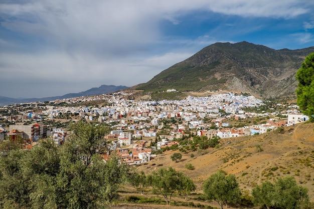 Landschap van heuvels bedekt met groen en gebouwen onder een bewolkte hemel en zonlicht Gratis Foto