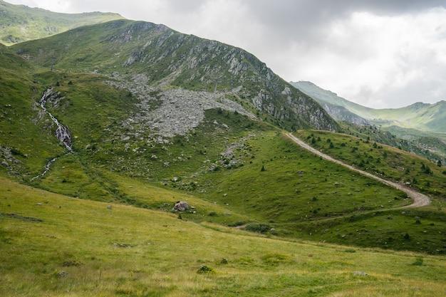 Landschap van heuvels bedekt met groen onder een blauwe lucht en zonlicht overdag Gratis Foto