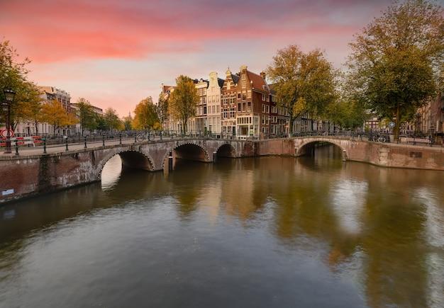Landschap van keizersgracht in amsterdam met de weerspiegeling van gebouwen en groene bomen Gratis Foto