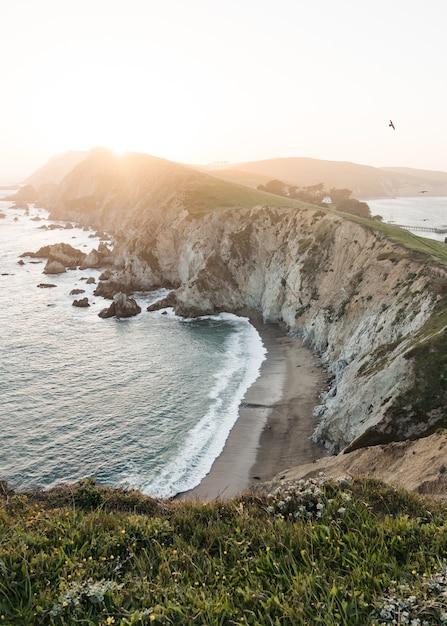 Landschap van oceaangolven die tijdens zonsopgang naar de rotsformatie gaan Gratis Foto