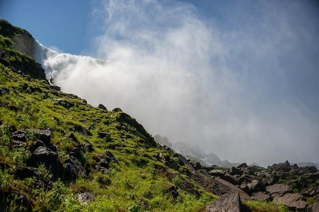 Landschap van rotsen bedekt met mossen met de niagara valt onder het zonlicht Gratis Foto