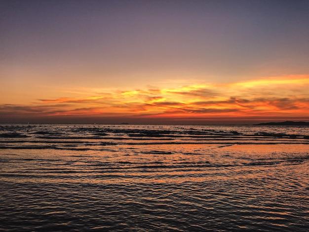 Landschap van zonsondergang op het strand met kalmerende golven van de oceaan Gratis Foto