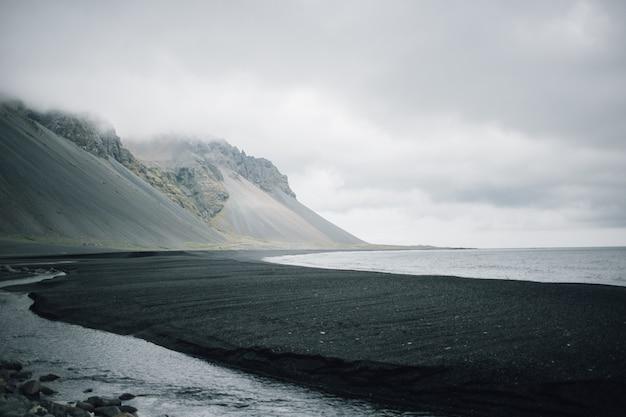 Landschap van zwart zandstrand vulkanisch strand Gratis Foto
