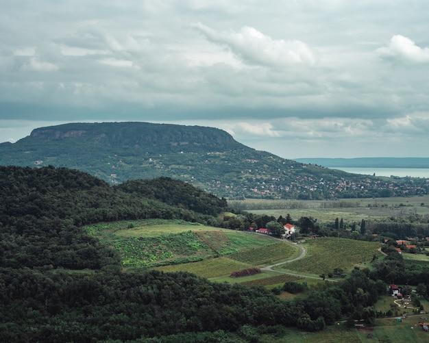 Landschapsmening van de velden en heuvels aan de oever van een meer op bewolkte dag Gratis Foto