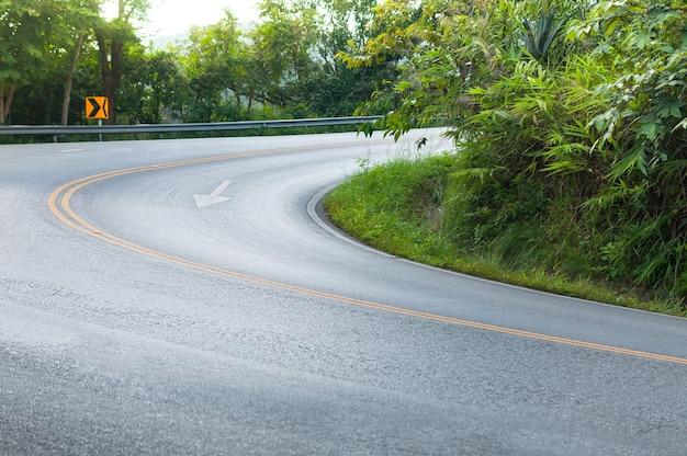 Landweggetje met aan beide zijden bomen, bocht van de weg naar berg Premium Foto